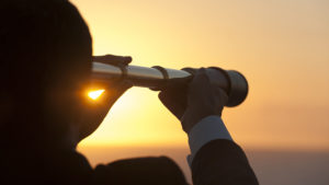 Businessman looking to the future with telescope
